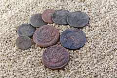 Old copper coins in the sand Royalty Free Stock Photos