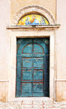 Old copper door. With scenery of the bible at the church  of St. Francesco in Vieste. The latin inscription explains the scenes Royalty Free Stock Photos