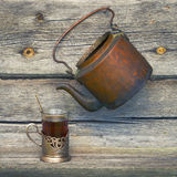 Old copper kettle and cup of tea Royalty Free Stock Photos