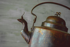 Old copper kettle. Fragment of an old copper kettle on the background of a concrete wall royalty free stock photography