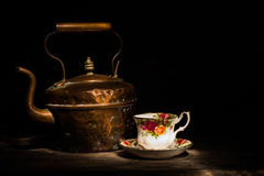 Old copper kettle and Roses china teacup stock photography