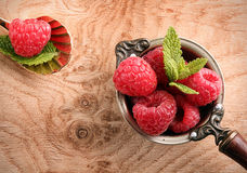 Old copper ladle and spoon with ripe raspberries Stock Photos
