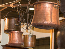 Old copper pots hanged on iron hooks Royalty Free Stock Image