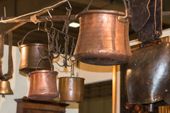 Old copper pots hanged on iron hooks Stock Image