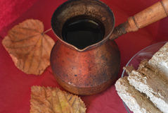 Old copper Turkish coffee pots, Middle Eastern sweets and autumn leaf on burgundy surface, top view Stock Photography