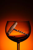 Old Cork Screwn in Wine Glass. An antique cork screw in a wine glass against a warm light to dark background Royalty Free Stock Image