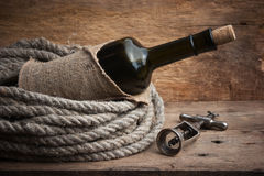 Old corkscrew and bottle of wine Stock Photography