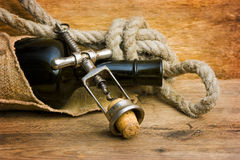 Old corkscrew with a cork and a bottle Royalty Free Stock Image