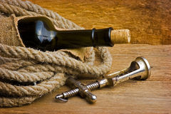 Old corkscrew with a cork and a bottle Royalty Free Stock Photos