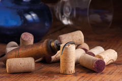 Old corkscrew and corks. Old corkscrew, corks, blue bottle and overturned glass on a wooden table, still life. Selective focus royalty free stock image