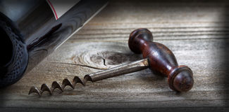 Old corkscrew and wine bottle on aged wood with vignette border Stock Image
