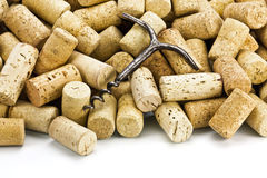 Old corkscrew and wine corks. Old corkscrew on a heap of wine stoppers from bottles Royalty Free Stock Photography
