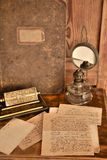 Old correspondence. Old letters and card, calendar, oil-lamp and book on wooden background Royalty Free Stock Photos