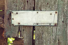 An old corroded banner on grungy wooden fence Royalty Free Stock Photography