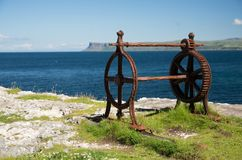 Old corroded iron winder with cogwheel, next to the sea, irish coast. Blue sea and sky, grass covered rocks, and superannuated iron wheels of an useless old Royalty Free Stock Images