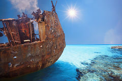 Old and Corroded metal ship at daylight with blue water Stock Images