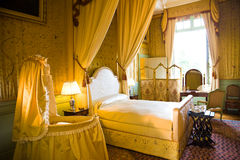 Old cot in luxury bedroom. Birth room from Cheverny Chateau, France Series Stock Photos