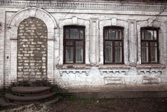 Old cottage. Three windows without doors the facade of speridi is white brick dirty Stock Photography