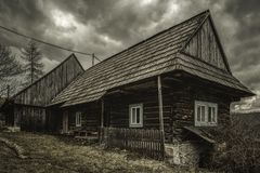 Old cottage and dark clouds. Old cottage in village Velke Borove and dark clouds over, Slovakia stock photo