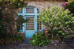 Old cottage with decorative plants at the front Stock Photography