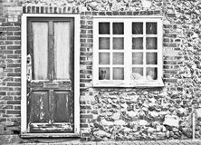 Old cottage. Front of an old cottage with peeling paint on the door and wondow Stock Images