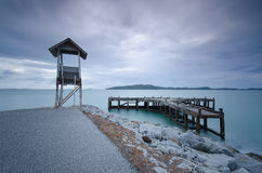 Old cottage and pier are near road. Old cottage and pier and cloudy day smooth movement Royalty Free Stock Photography