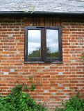 Old cottage window. Old wooden window of a cottage bungalow against a red brick wall.  Sunlight reflecting off the glass Royalty Free Stock Images