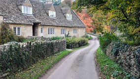 Old Cottages on a Country Road in Autumn. Autumn Scene of a Row of Old Stone Cottages on a Country Road in Rural England Royalty Free Stock Photography