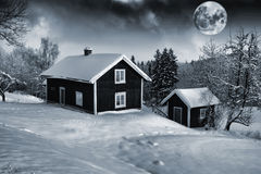 Old cottages and full moon in winter landscape Stock Image