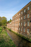 Old cotton mill beside river Stock Images