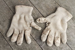 Old cotton work gloves on weathered wood. Stock Photos