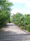 Old Country Bridge. Old swinging bridge made of wood located in the country with blue skies Stock Photo