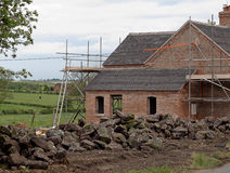Old Country Cottage Under Renovation. Old country house being renovated with scaffolding in place stock image
