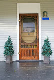Old country door with 2 Christmas trees on each side Royalty Free Stock Photo