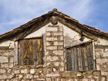 Old Country House. Detail of a country house with stone facade and asymmetric wood windows Stock Photo