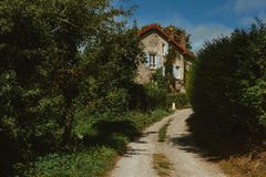 Old country house with blue shutters and gravel road in Normandy, France on a sunny day. Beautiful countryside, french Royalty Free Stock Photo