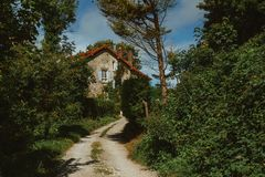 Old country house with blue shutters and gravel road in Normandy, France on a sunny day. Beautiful countryside, french Royalty Free Stock Photography