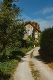 Old country house with blue shutters and gravel road in Normandy, France on a sunny day. Beautiful countryside, french Stock Photography