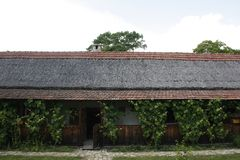 Old country house with red tiles roof, white walls, wooden porch royalty free stock photography