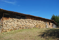 Old country house stacked firewood. Old country wooden house stacked firewood, meadow, blue sky royalty free stock photos