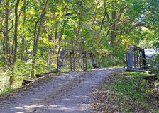 The old country lane. Dirt road with old metal bridge across a creek Stock Photos