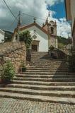Church facade and steeple on top of stone staircase. Old countryside church facade and steeple on top of stone staircase, in a sunny day at Alvoco da Serra. A royalty free stock photos