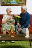 Old couple. Senior man offering some flower to his lady love Stock Image