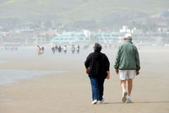 Old Couple on the Beach. An older couple walks along a busy beach Royalty Free Stock Photography