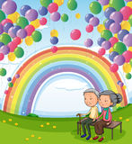 An old couple below the floating balloons and the rainbow Royalty Free Stock Image