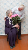 Old couple and big bouquet of pink roses Royalty Free Stock Photography