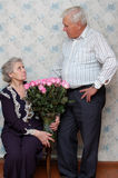 Old couple and big bouquet of pink roses Stock Image