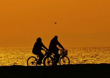 Old Couple Biking Sunset Stock Photo