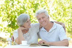 Old couple with book. Beautiful old couple with book in summer royalty free stock photos