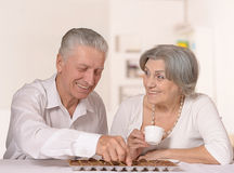 Old couple with chocolate candies Stock Photos